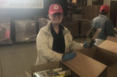 A woman wearing a hat and coat smiles for the camera while packing a cardboard box with food.