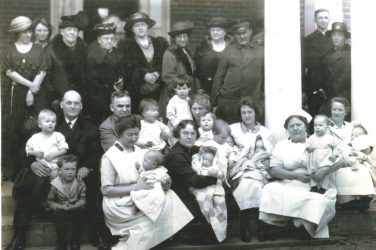 A group of adults, nurses and babies are seated and standing on the front porch of a building.