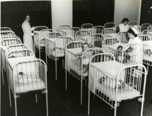 An old fashioned nursery with rows of babies in cribs and three nurses caring for the babies.