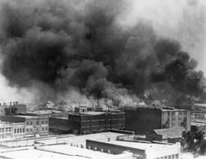 Black and white photo of city buildings, some with thick clouds of smoke billowing from the roofs
