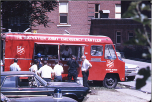 A red Salvation Army canteen truck distributing food to men