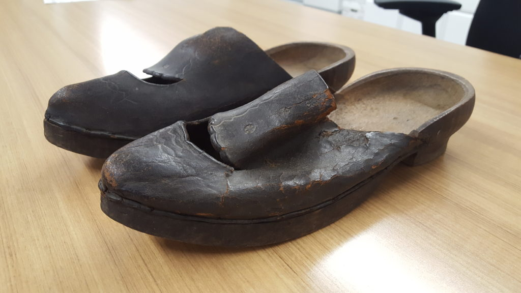 A pair of clogs with wood soles and brown leather upper