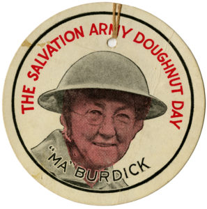 "A round paper tag featuring a picture of a woman wearing a helmet. Text reads ""The Salvation Army Doughnut Day Ma Burdick"""