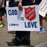 """Person holding sign """"God is Love 1 John 4:8"""" Sign features Red Shield logo"""