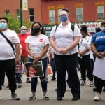 Four people wearing facemasks and Salvation Army branded clothing stand in a crowd of other people.