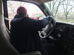 A person sitting in the drivers seat of a cargo van