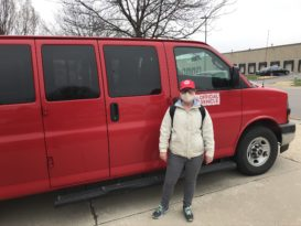 Person standing outside red cargo van. Person wears EDS hat and face mask