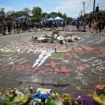 People stand around a memorial featuring flowers and messages which are painted on a street.