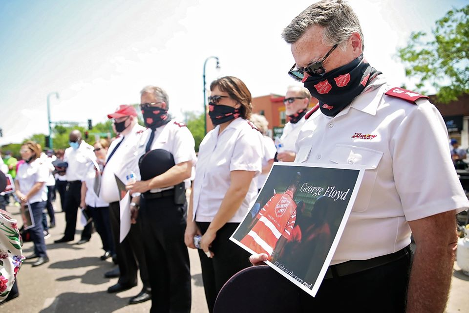 Salvation Army offiers wearing face masks bow their heads in prayer, one holds sign honoring George Floyd