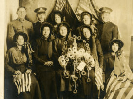 A group of men and women posing with US flags and a wreath decorated with glowers and doughnuts