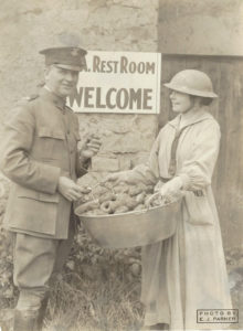 A man in military uniform poses with a woman holding a tub of doughnuts