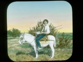 A man holding an old fashioned camera while sitting on the back of a mule