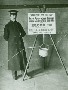 """Black and white photograph of early 1900s male Salvationist wearing hat and long overcoat. The man stands next to a kettle stand with placard that reads """"Keep the Pot Boiling. Free Christmas Dinner to 25,000 Poor Under the Auspices of The Salvation Army. Every Little Helps"""""""