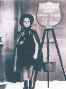 Black and white photograph showing a young Shirley Temple wearing a dress, cape and Salvaiton Army bonnet. Temple is holding a handbell and standing next to a kettle stand.