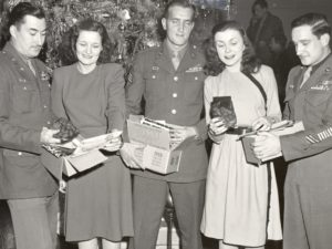 Black and white photo of three World War II soldiers and two women. The group opens care packages given to the men. The group stands in front of a decorated Christmas Tree