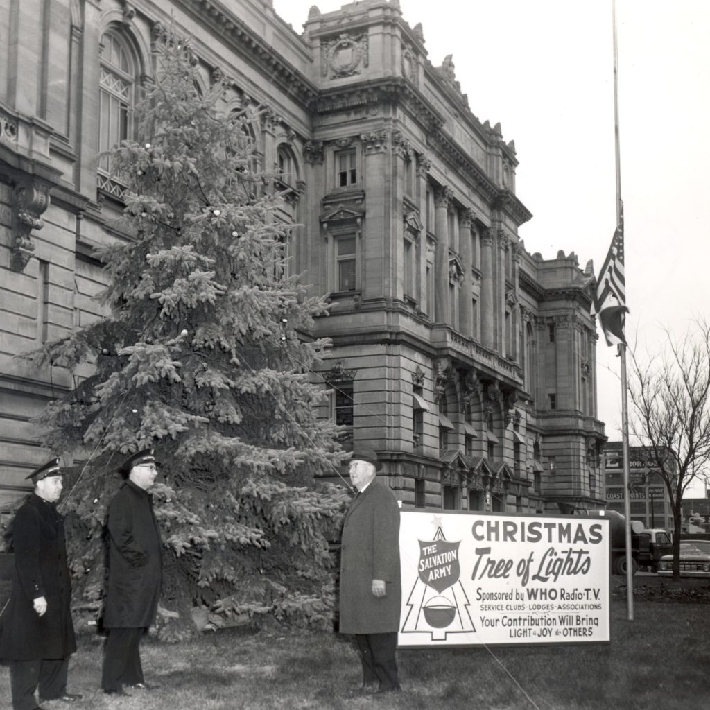 Two Salvation Army officers and one man wearing a suit stand in front of a Christmas tree that is located in front of a Des Moines, IA public building. A sign next to the tree informs readers that this is the Tree of Lights.