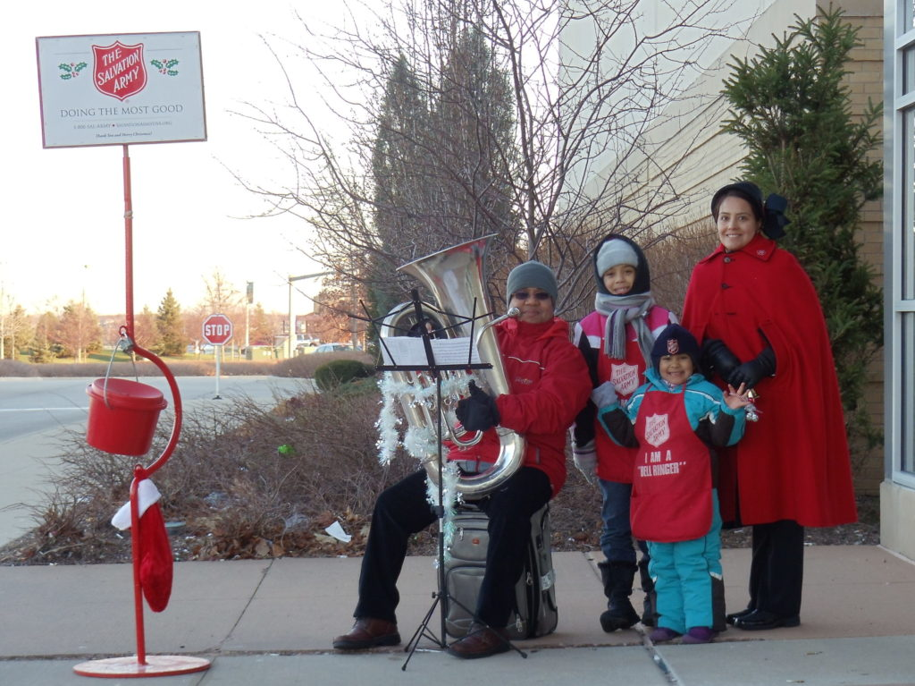 Color photo of a family working as bellringers at a kettle stand. The father is seated and plays the tuba, mother wears a vintage Salvation Army bonnet and red cape, the two children wear bellringer aprons and hold handbells.