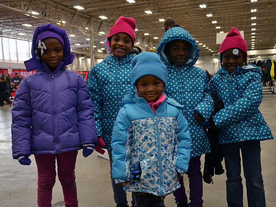 Color photo of five children wearing winter coats and hats. Racks of new coats can be seen in the background.