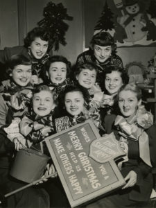 """Black and white photo of a group of glamourous young women from 1949. The women are from a modeling agency. They hold their kettle stand placard, kettle and bell. The sign reads: """"The Salvation Army wishes you a Merry Christmas. Help us Make Others Happy."""""""