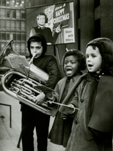 """Black and white photo of three children. A boy plays a tuba while two girls sing. The children stand in front of a kettle stand with placard that reads """"Give a Happy Christmas. Share with Others."""""""