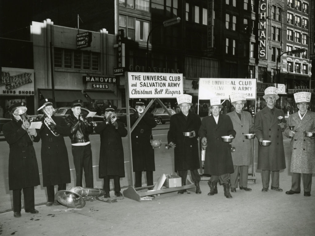 """A group of men stand in a line outside on a city street sidewalk. The men wear hats and topcoats. Some men wear Salvation Army uniforms and are playing brass instruments. The other men have paper signs taped to their hats and hold metal pans to collect donations. A sign on top of the kettle stand reads: """"The Universal Club and Salvaiton Army Christmas Bell Ringers"""""""