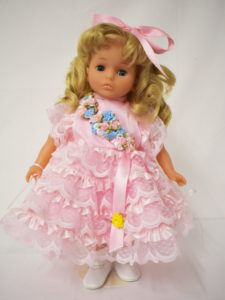 A blonde haired, blue eyed doll wearing a frilly pink dress
