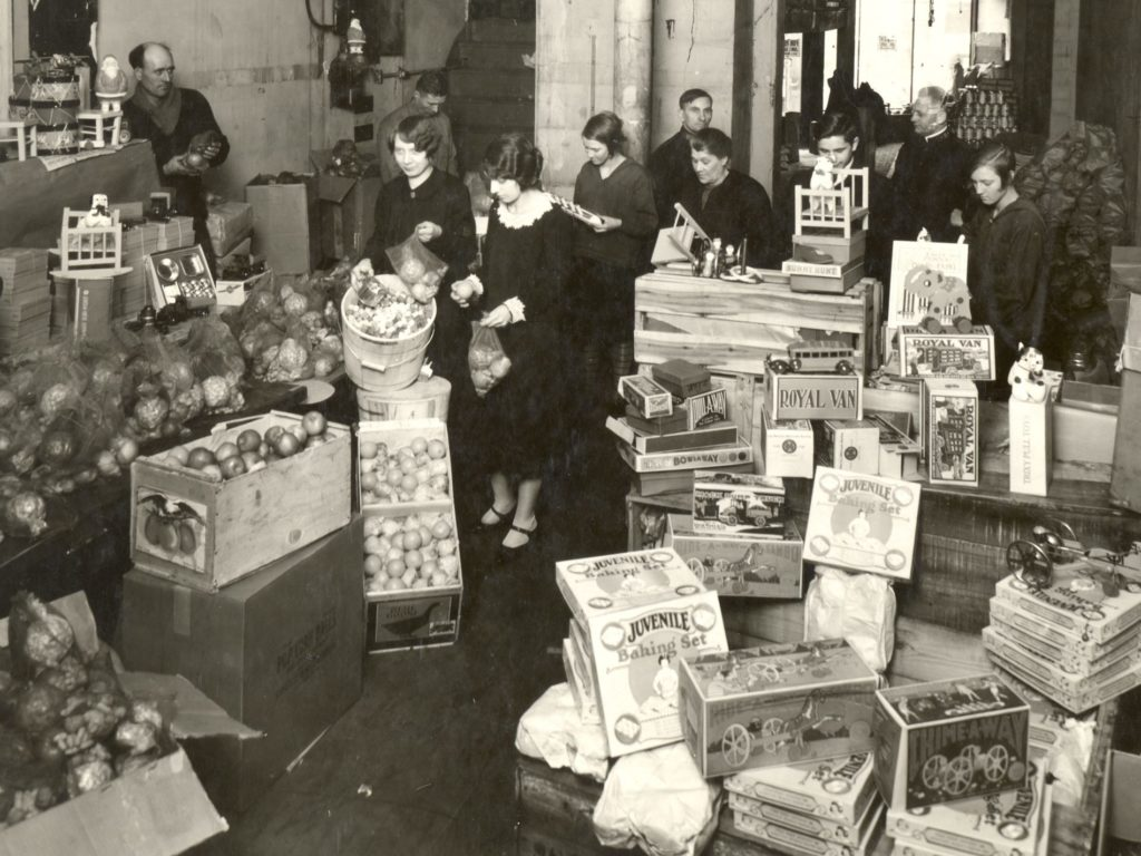 Black and white photo from the 1930s showing parents selecting food and Christmas presents for their children