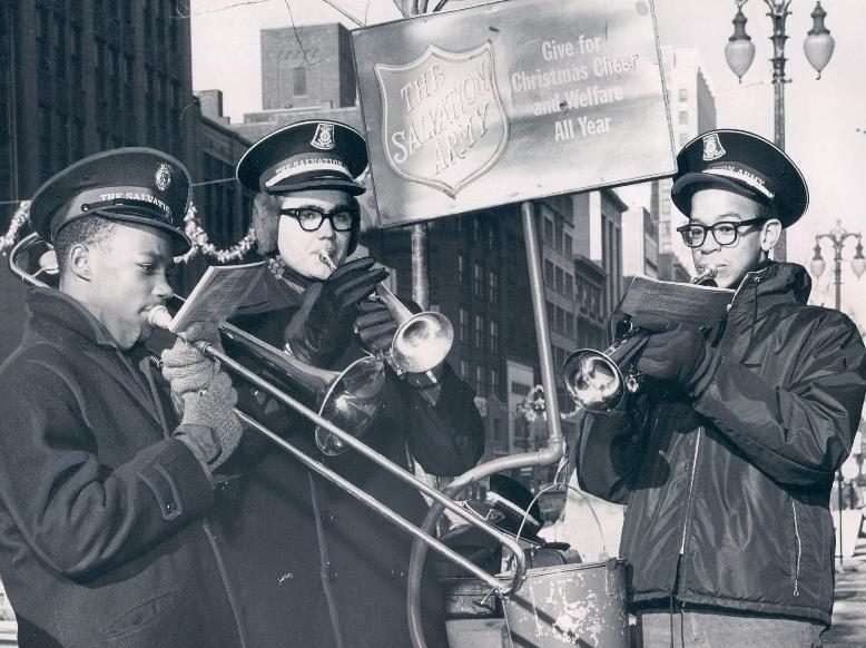 Three young men play brass instruments while standing in front of a kettle stand in Detroit, MI in 1963. One man plays the trombone and the other two play cornettes.