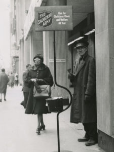 Black and white photograph of an older man wearing a Salvation Army hat and overcoat ringing a bell near a kettle stand. Shoppers pass by on a city street.