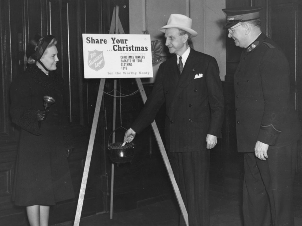 """Black and white photograph of male and female Salvation Army officers watching as a man in a suit and hat places a bill into the kettle. The placard reads: """"Share your Christmas. Christmas Dinners Baskets of Food Clothing Toys for the Worthy Needy."""""""