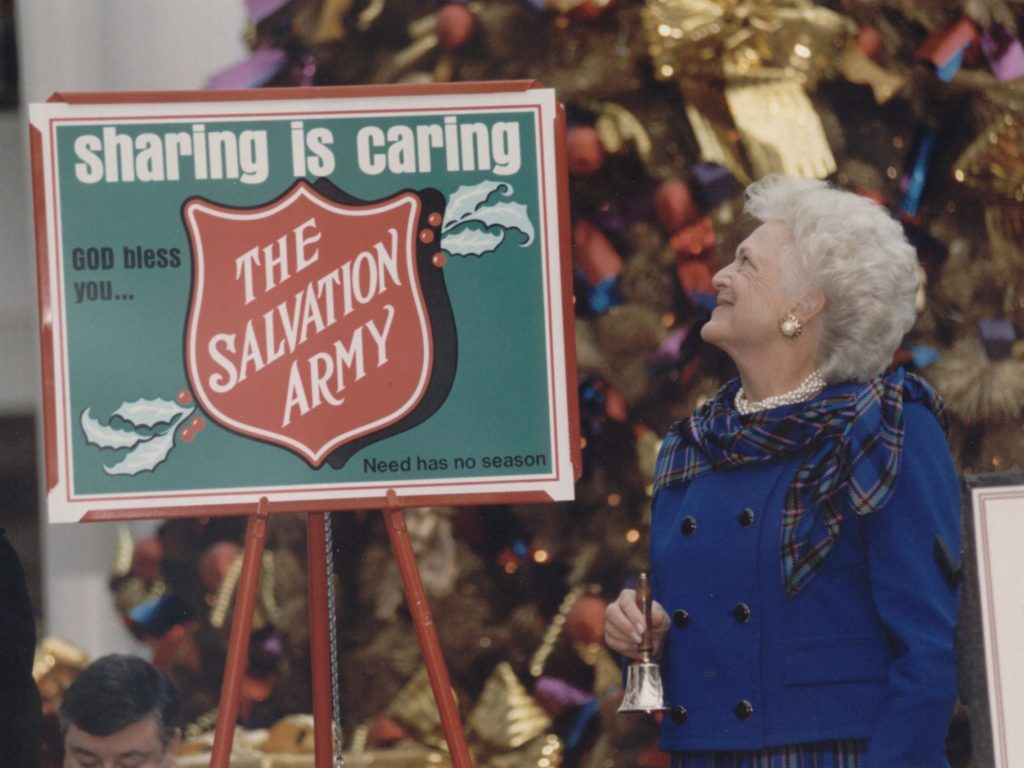 "Color photograph showing former First Lady Barbara Bush holding a handbell. Mrs. Bush is looking at a kettlestand placard that reads ""Sharing is Caring God bless you... The Salvation Army Need has no season"""