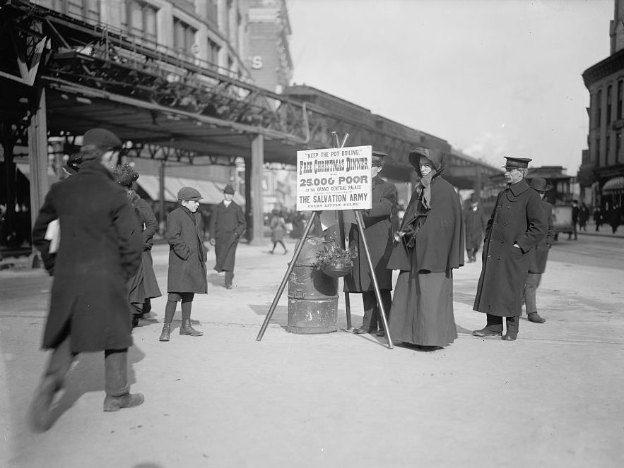 """Black and white photograph showing an early 1900s street scene. Two male and one female Salvation Army members stand next to a tripod with iron kettle and placard. The woman rings a handbell. The placard reads """"Keep the Pot Boiling. Free Christmas Dinner for 25,000 Poor at the Grand Central Palace The Salvation Army Every Little Helps"""""""