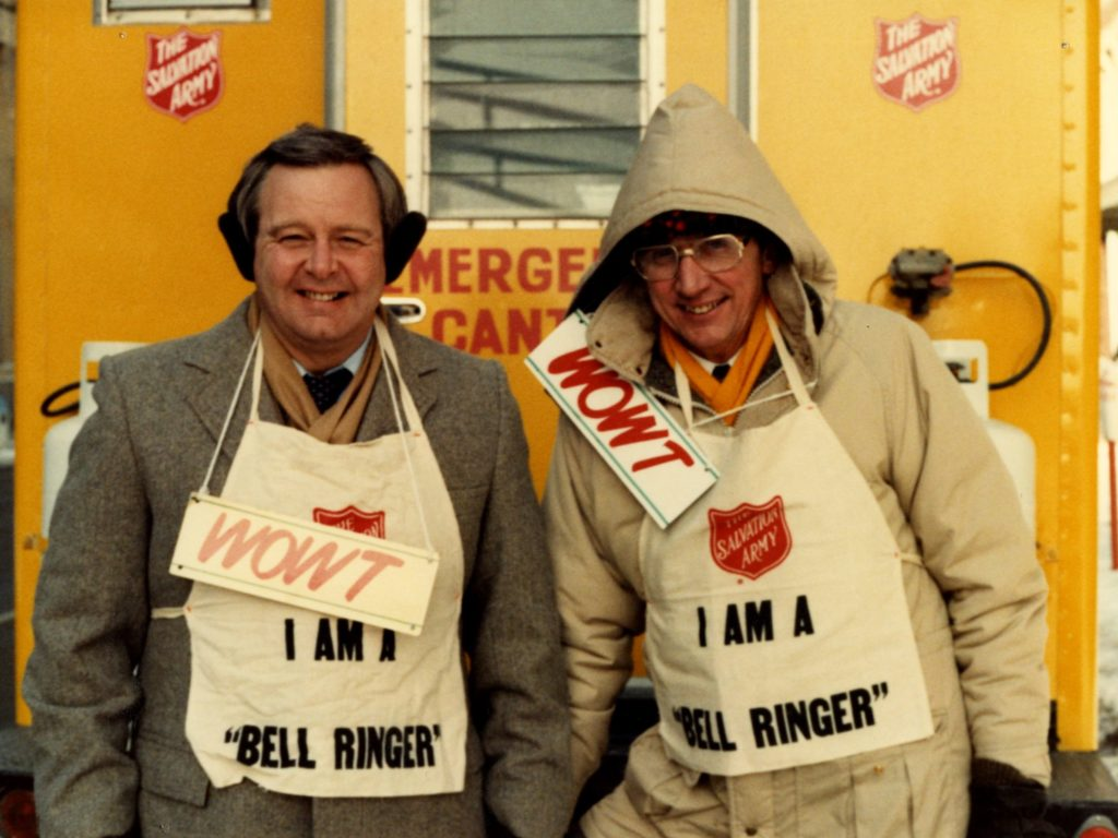 "Color photo of two men wearing winter coats, aprons which read ""I am a bell ringer"" and ""WOWT"" signs around their necks. The men stand in front of a yellow Salvation Army canteen truck"
