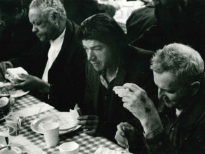 Three men seated at a table eating dinner