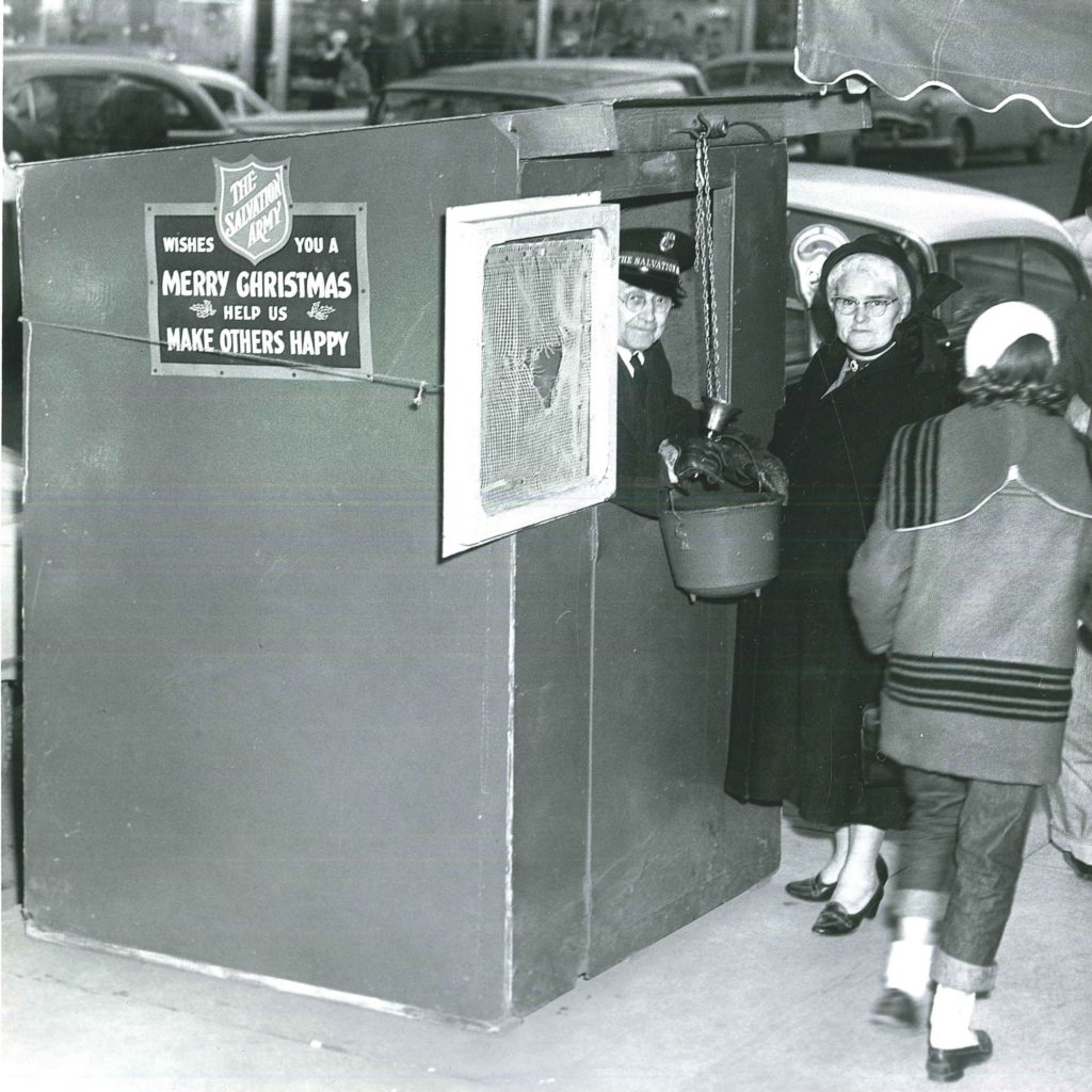 Black and white photo of a man peaking out from inside a kettle booth while a woman stands outside. A kettle is suspended in front of the booth on a rope. A girl wearing a winter coat passes in front of them. Cars and shops can be seen in the background
