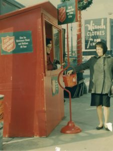 Color photo showing a red wood booth with a Salvation Army Red Kettle stand in front. A bellringer can be seen at the window of the booth. A woman places money into the kettle.