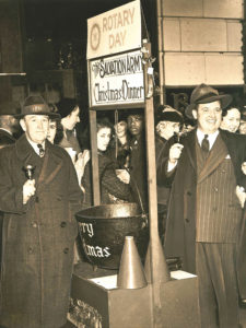 "Black and white photograph showing two men wearing suits and fedora style hats, holding hand bells. The men stand on either side of an iron kettle with placard above that reads ""Roatary Day The Salvation Army Christmas Dinner"""