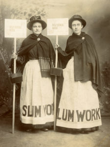 "Black and white photograph of two women wearing early 1900s dresses, flat brimmed hats, blanket shawls, and aprons with ""Slum Work"" printed at the hem. The women hold signs that read ""Self-Denial Week"" the signs are on long poles and have a metal collection box attached to the pole."