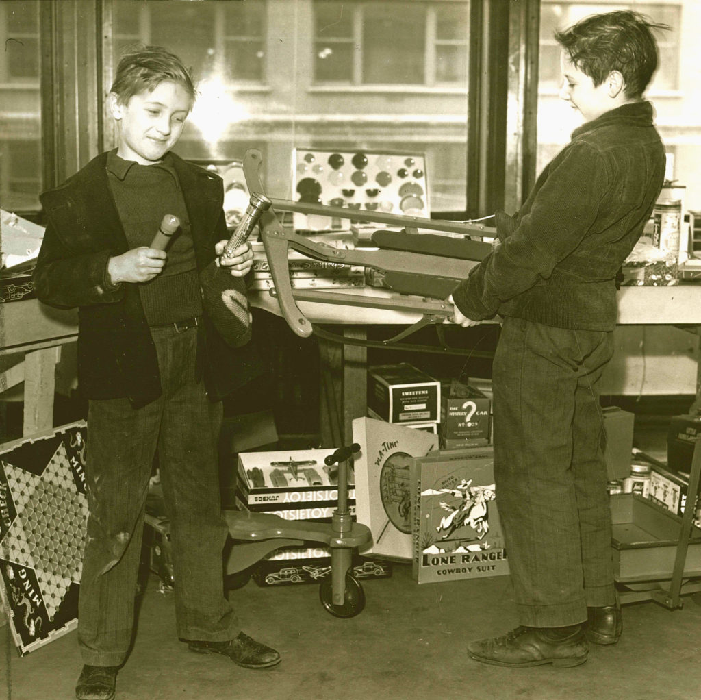 Black and white photo of two boys selecting the toys they would like to receive for Christmas. One boy holds a sled and the other two flashlights.