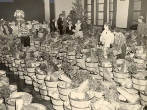 Black and white photo showing rows of bushell baskets filled with food and people packing the baskets. A Christmas tree is in the background
