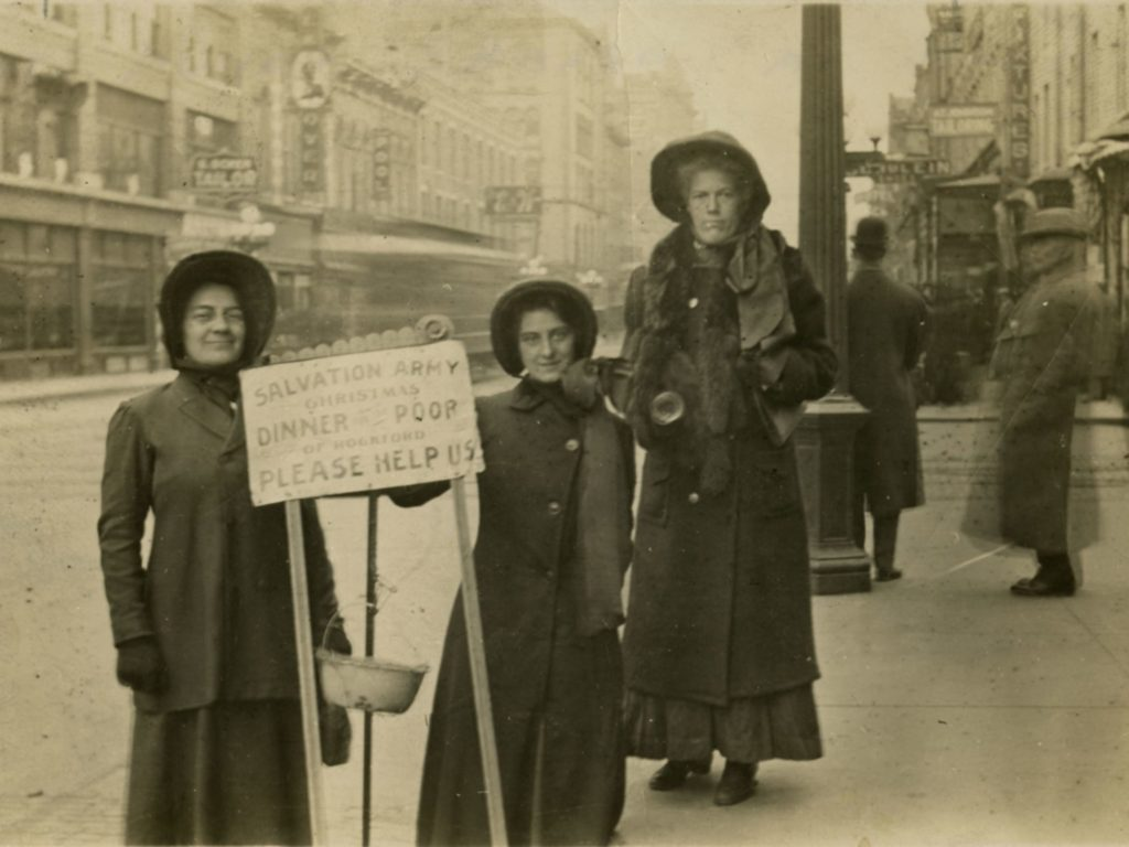 Black and white photograph showing three female Salvationists wearing overcoats and Salvaiton Army bonnets. The three women stand around a kettle stand. One woman holds a handbell. The main street of an early 1900s Midwestern city can be seen behind them.
