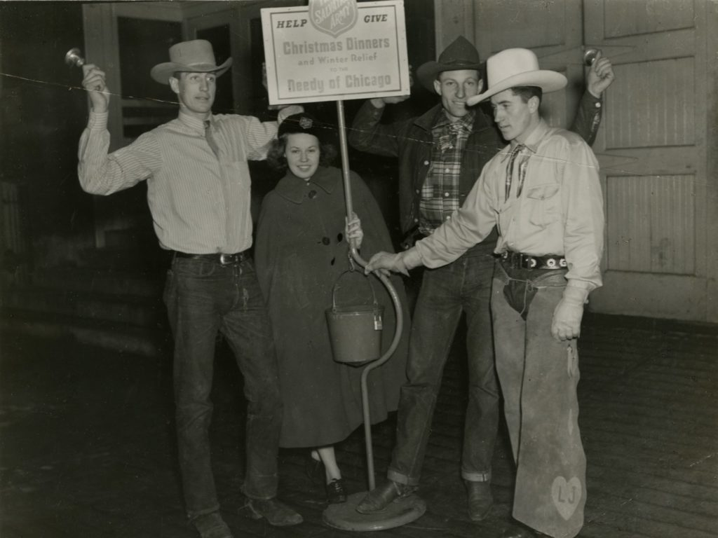 Black and white photo showing three men wearing cowboy style clothing and one female Salvationist who is wearing a cape. The four stand around a red kettle stand. Two of the men are ringing handbells.