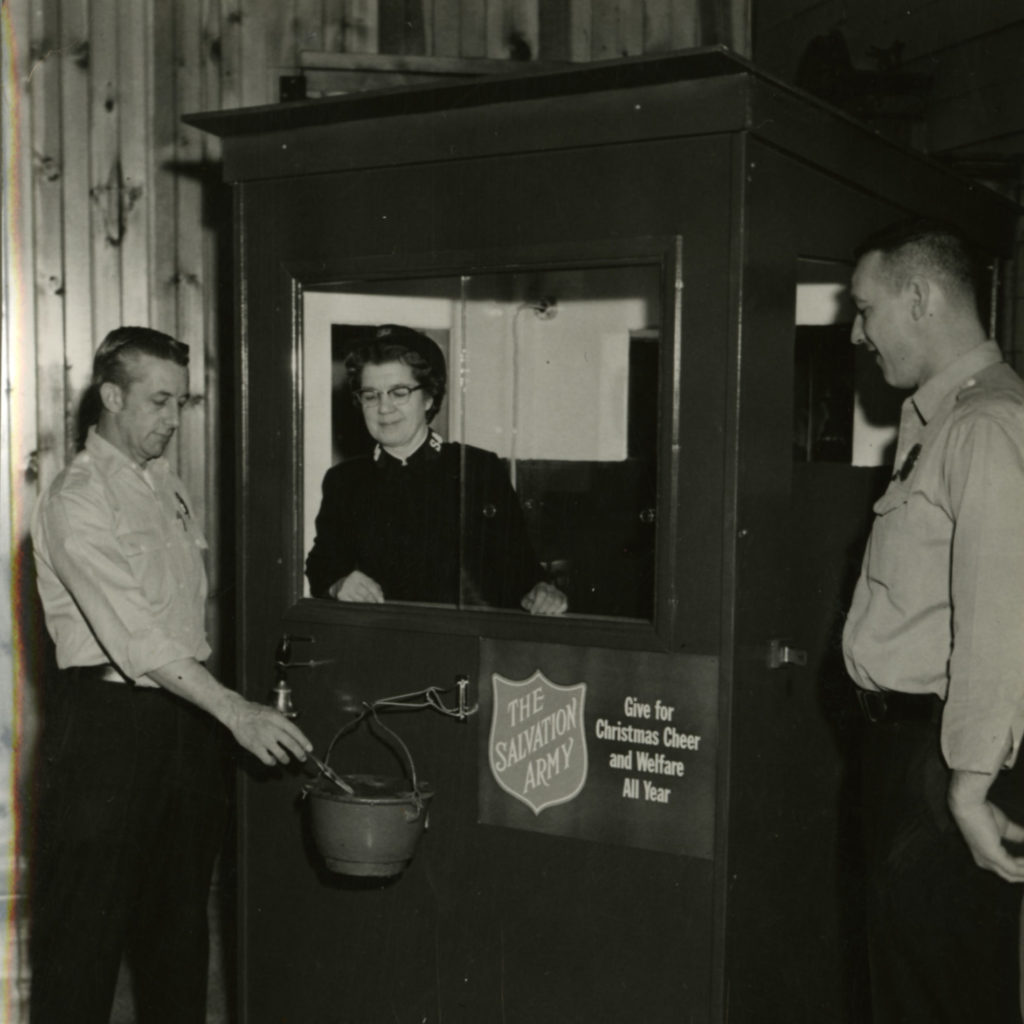 Black and white photo of two men in Firemen's uniforms (uniform button down shirts and trousers) while a female Salvationist stands inside a kettle hut. The kettle is attached on a hook to the front of the hut.