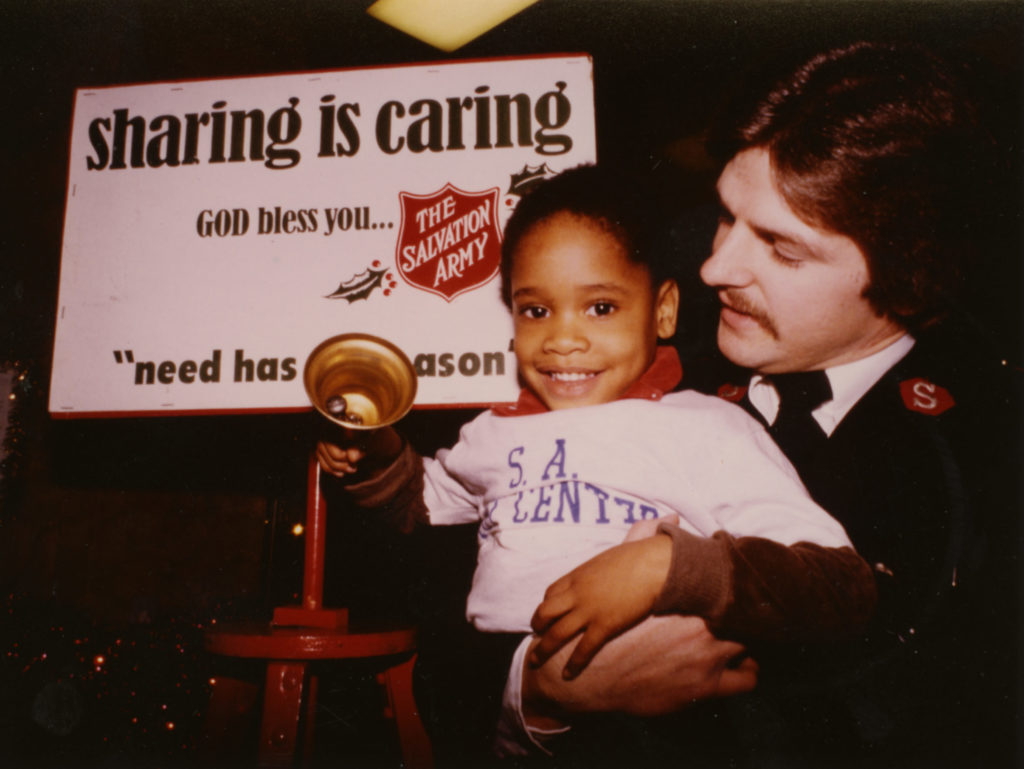 "Color photograph of a Salvation Army officer holding a little girl. The girl holds a bell. The placard on the kettle stand behind them reads: ""Sharing is Caring. God Bless You. Need has no season."""