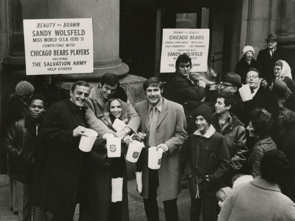 Black and white photograph showing a street scene from the early 1970s. Several men pose with a woman while others look on. The central figures all hold plastic tubs which bear The Salvation Army Red Shield Logo. Signs in the background inform viewers that these are members of the Chicago Bears football team and Miss World USA Sandy Wolsfeld.