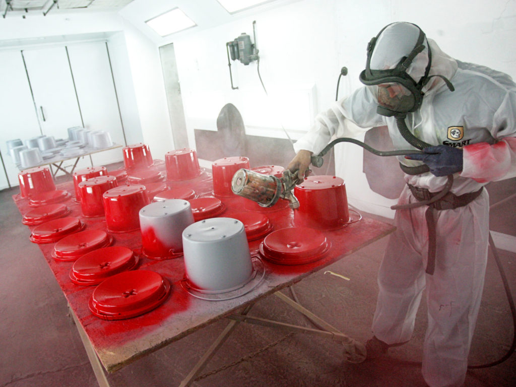 Color photo of a man spray painting kettles with red paint