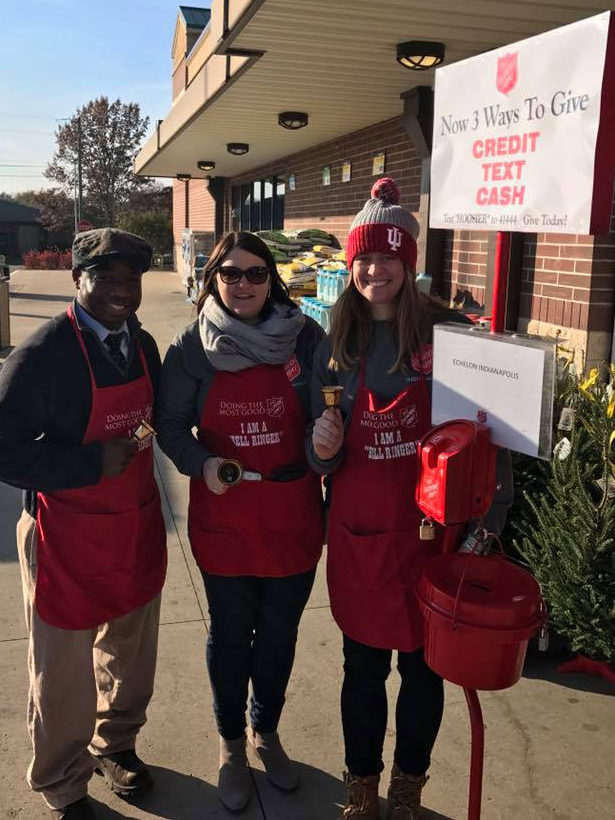 Color photo of three young adults wearing red Salvation Army bellringer aprons. They all hold hand bells. They stand next to a kettle stand.