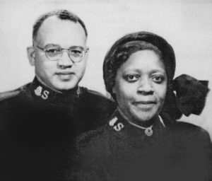 Portrait photograph of a Black man and woman wearing Salvation Army officer uniforms.