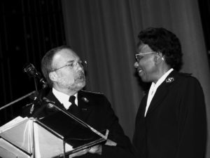 Photograph of a black woman wearing a Salvation Army uniform talking at a podium with a man also wearing a Salvation Army uniform