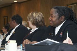 Photograph showing three women seated in a wood paneled conference room. Major Janice Love is on the far right and is smiling.
